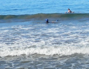 Kathleen trying to get the fins off in the surf