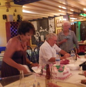 Christine cutting her cake with the /Senor in the back ground